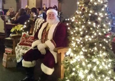Santa Dan Next To Lit Up Christmas Tree