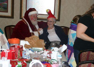Santa Dan Holding Elderly Lady's Hand While Both Smile